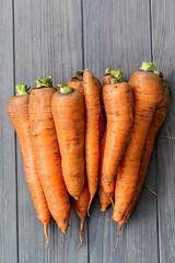 Ripe orange carrot on gray wooden background