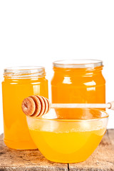 Background with natural bee honey in glass jars and a bowl