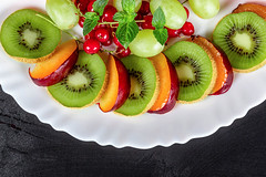 Fresh kiwis, plums, grapes and red currants on a white plate, top view