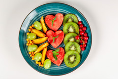 Sliced ripe fresh fruit and berries in a plate on a white background, top view