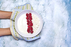 Woman holding a plate of healthy dieting breakfast - cottage cheese and sour cream with raspberries