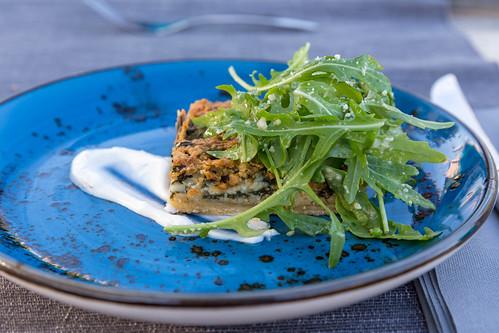Summer quiche with rocket salad on a blue plate at Villa Vegana restaurant in Selva, Mallorca