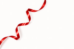 A single red ribbon on the white background with copy space