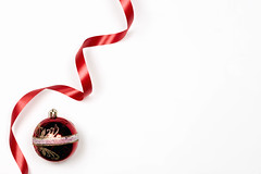 A red decorative Christmas ball and ribbon with on white background with copy space