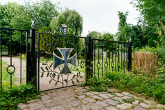 Entrance to the German cemetery with the Iron Cross on the front gate