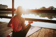 Woman working out on the wooden terrace on lake