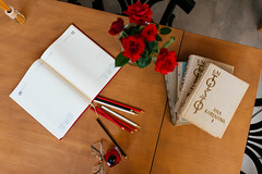 Books, pencils and roses on the table
