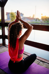 Woman meditating on wooden terrace