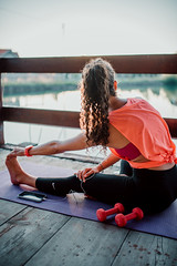 Woman stretching on wooden terrace