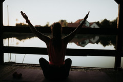 Woman doing yoga on the wooden terrace on lake