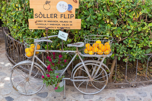 Metal bicycle with flowers in pots and oranges in baskets. Orange juice and ice