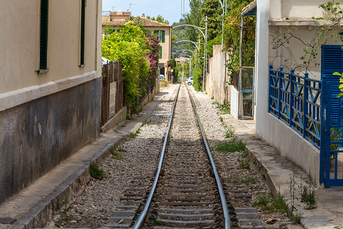 Perspective with rail tracks between houses with blooming gardens in Sóller on Majorca