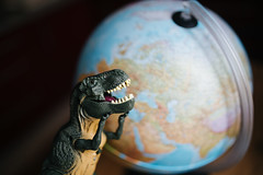 Plastic dinosaur figure in front of a globe