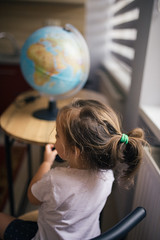 Girl sitting in front of a globe on a geography class