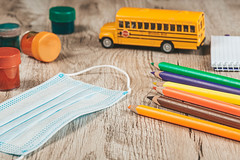 Colored pencils, paints, mask and school bus on wooden background