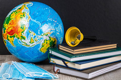Quarantine restrictions in schools around the world concept. Globe, books and masks