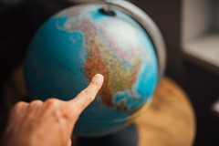 Finger pointing at the globe map