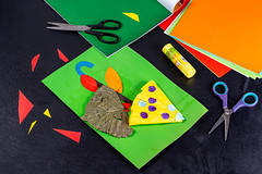 Children's handicraft with colored paper, glue and scissors on a black background
