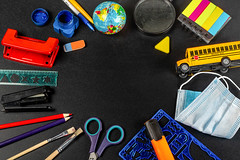 Top view, frame of school supplies with a medical mask on a black background