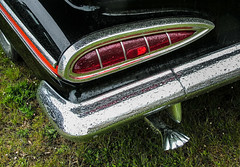 Vintage Chevrolet Impala tail light and scallop-shaped exhaust pipe
