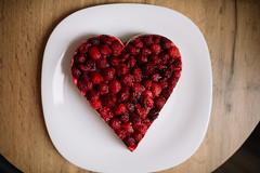 Raspberry topping on the heart shaped piece of cake on a plate