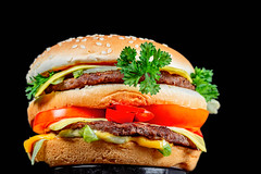 Big burger with vegetables and cutlets on a black background