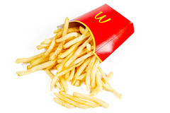 French fries scattered on a white background with a red box