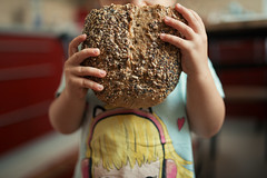 Toddler holding rye bread with sesame seeds