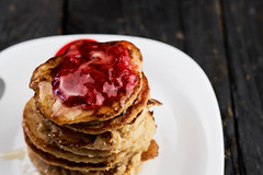 Plate with pancakes and strawberry jam on dark wood background