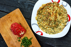 Overhead shot of herbs based omelet and wooden cutting board with slices of tomato and scallions