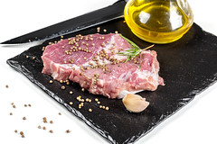 Fresh raw steak with spices, olive oil, garlic and knife