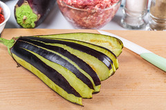 Sliced fresh eggplant on wooden kitchen board and ingredients for filling