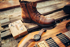 Man boots, guitar pedal, guitar and watch on wooden platform.