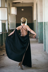 Model walking down the hall in an abandoned building.