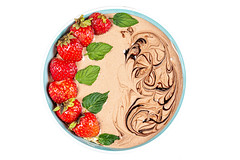 Top view, bowl of oatmeal with yogurt, strawberries and mint
