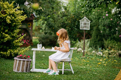 Girl sitting on a chair near white table in the backyard.