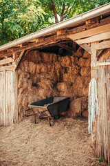 Haybarn with wheelbarrow parked inside.