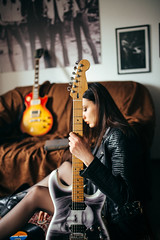 Rock girl in leather jacket with electric guitar in her music room.