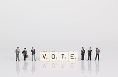 People standing next to vote text