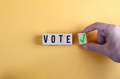 Concept of voting yes or positive vote. Male hand placing wooden cube with check mark yes symbol next to the cubes with the word vote