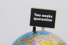 Man with a suitcase standing on globe with Two weeks quarantine sign
