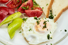 Close-up view of fried egg with fresh vegetables and toast