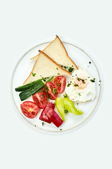 Fried breakfast with egg, tomatoes, bell pepper cucumber and toasts