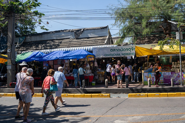 Bangkok, Thailand - November 30, 2019:  Shoppers cross the street to enter the famous Chatuchak Weekend Market to visit all of the vendors and stalls