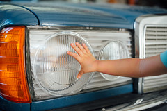 Young kid touching car headlights.
