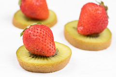 Sliced Kiwi and Strawberries arranged on the white table