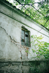 Damaged wall and window of the old abandoned house.