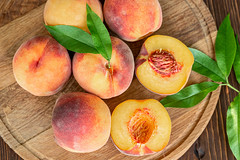 Top view, peaches with leaves on wooden background