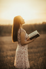 Beautiful girl in glamour dress holding a book outdoors at the sunset.