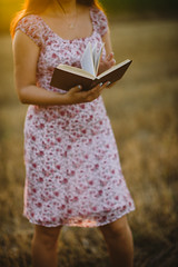 Glamour girl holding a book in nature.